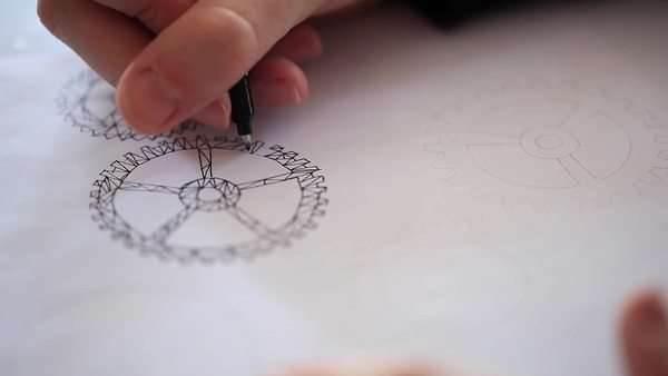 Close-up of a man drawing a sketch of abstract gear Royalty-free stock video