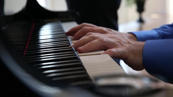 Handheld shot of man playing the piano Royalty-free stock video
