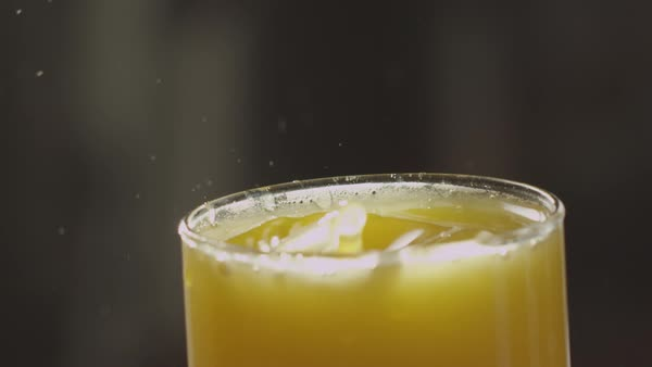 Macro shot of drops of orange juice splashing in a glass in slow motion Royalty-free stock video