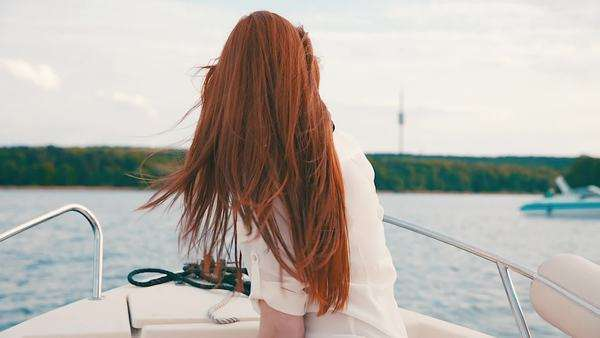 Pretty woman with beautiful red hair on motorboat Royalty-free stock video