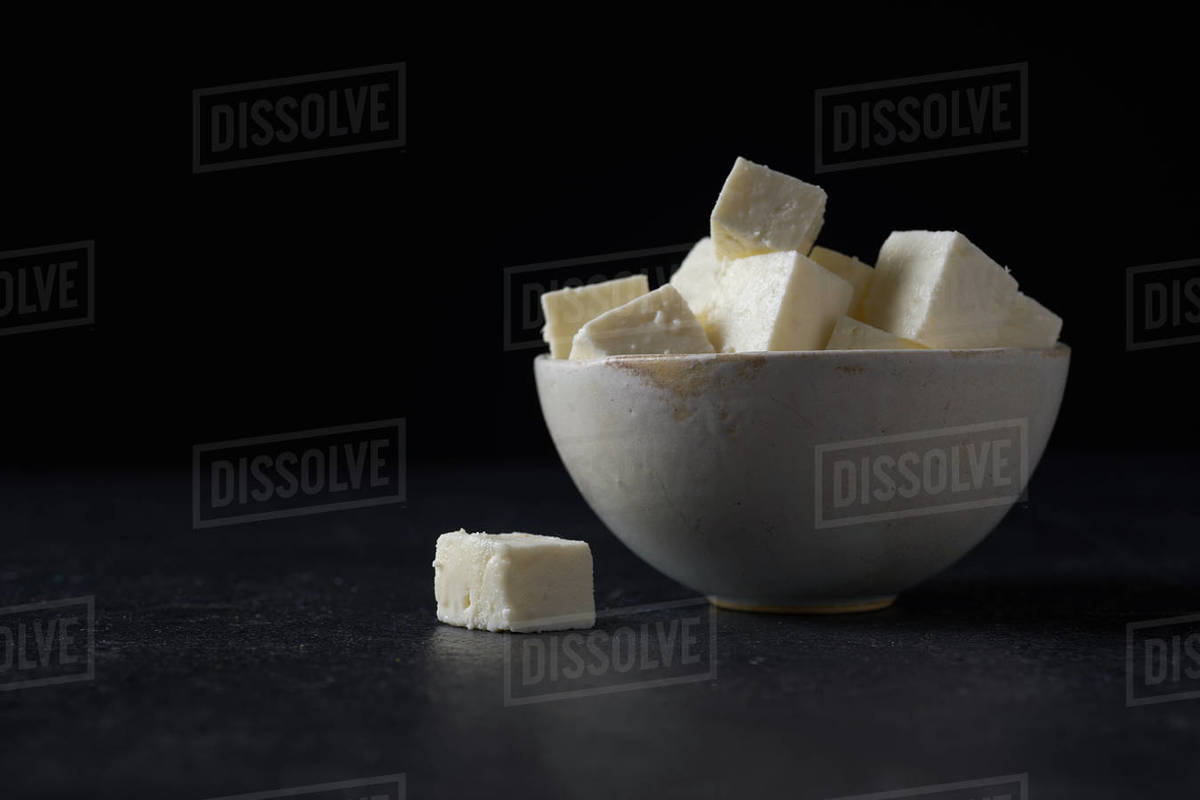 Traditional indian cheese paneer. Vegetarian homemade soft cheese in cheesecloth on dark background. Royalty-free stock photo