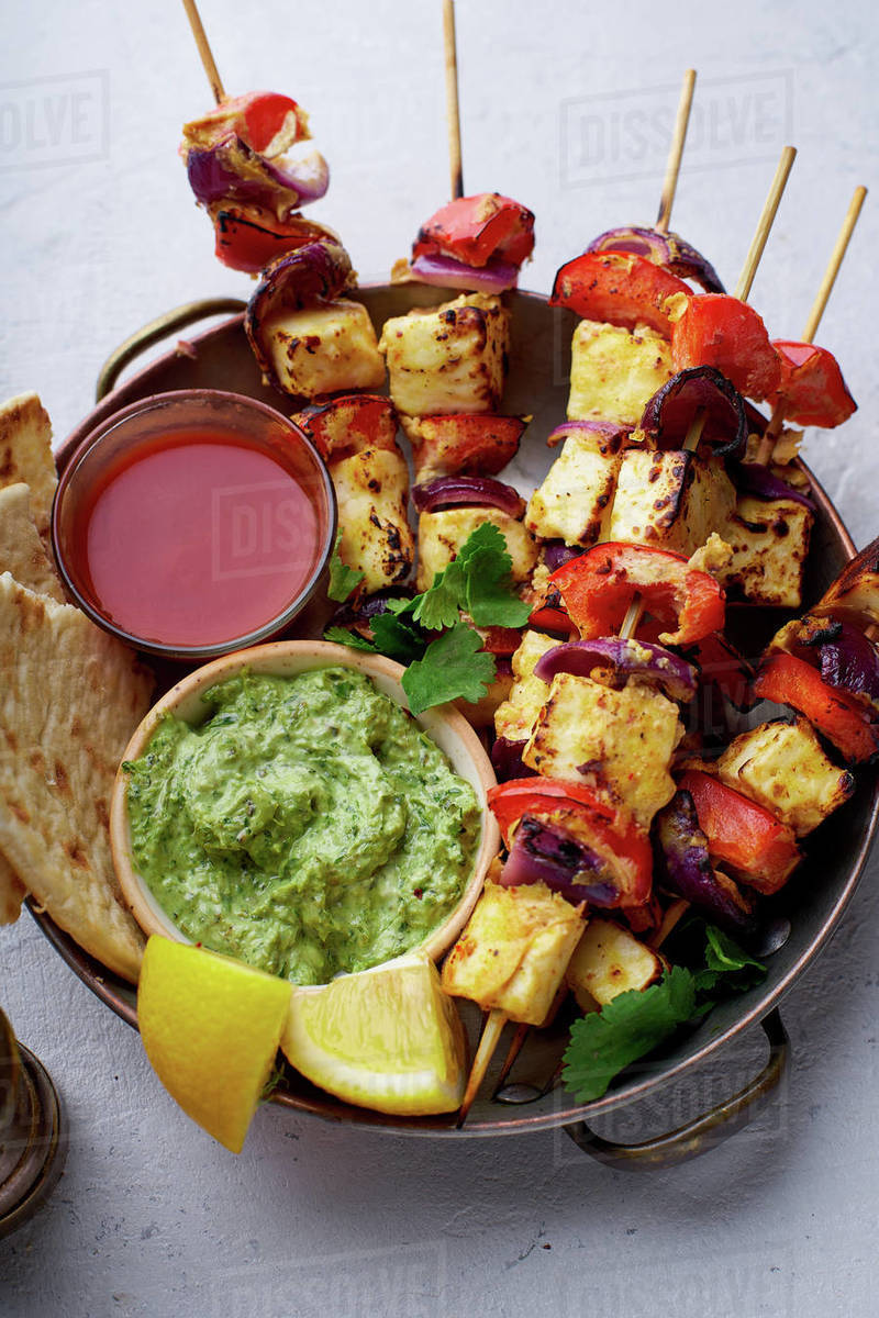 Paneer tikka starter kebabs with mint chutney and chapati. Traditional indian cuisine, grilled cheese skewers with onion and bell pepper slices. Vegetarian dish marinated in tikka sauce. Royalty-free stock photo