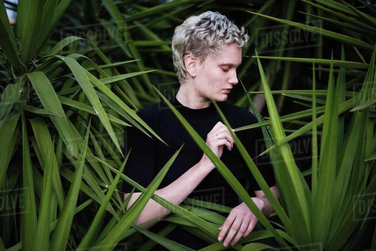 Short hair blonde wearing black between leafs Royalty-free stock photo