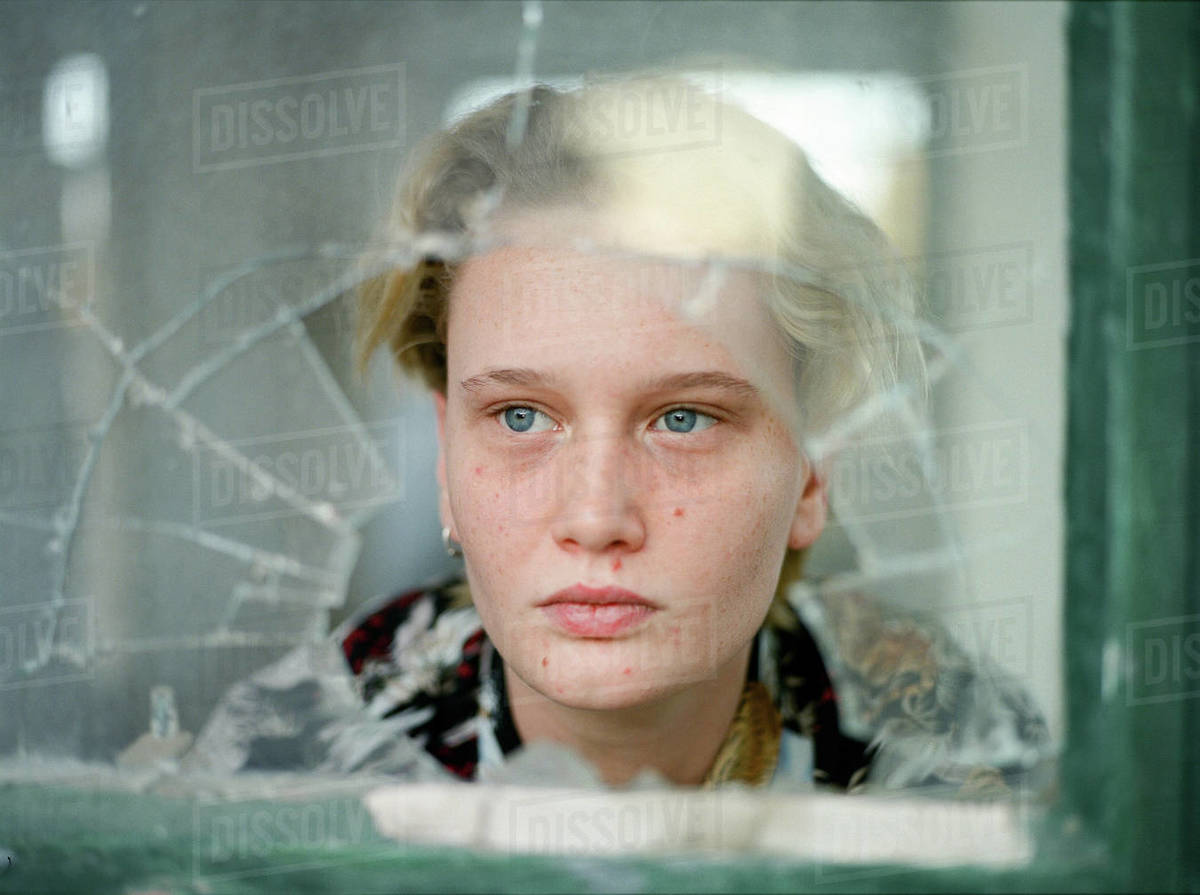 Female with short hair behind broken window looking far  Royalty-free stock photo