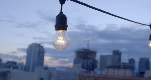 Electric Light Bulb Hangs In Front Of The Downtown Skyline Los Angeles California At Sunset Recorded Slow Motion Stock Video Footage Dissolve