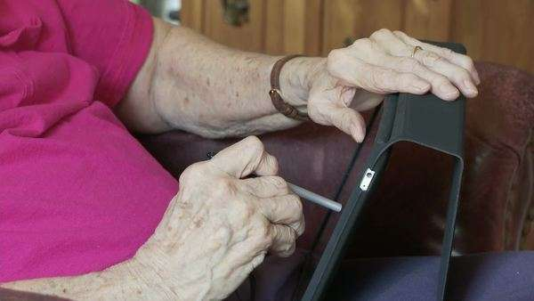 Elderly woman's hands, crippled with arthritis, use a touch-screen tablet computer with a stylus. Arthritis has taken away this person's ability to manipulate the touch screen with her fingers. Royalty-free stock video