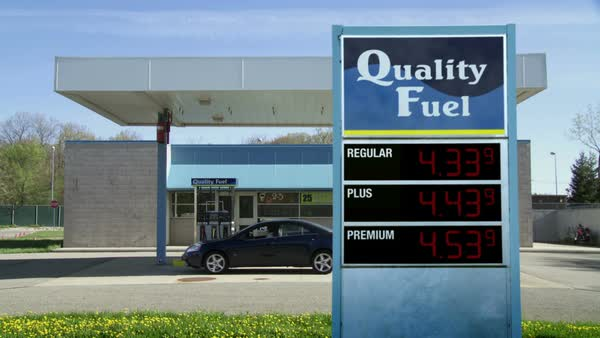 Car drives up to gas pumps at unbranded service station.  Gas prices on sign rise from 3.00 to more than 6.00 (currency not shown so can be used internationally).  Locked off shot. Royalty-free stock video