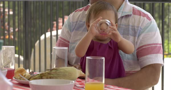 Infant daughter sits on father's lap and drinks pink lemonade from a plastic glass at a BBQ with friends and family Royalty-free stock video