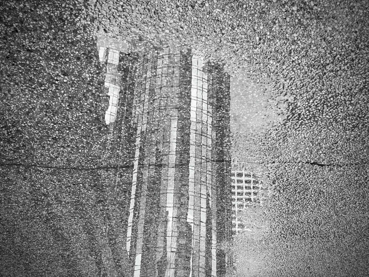 LOS ANGELES, CA, MAR 2020: reflection of Westin Bonaventure hotel in puddle after rain in Downtown. Black and white Royalty-free stock photo