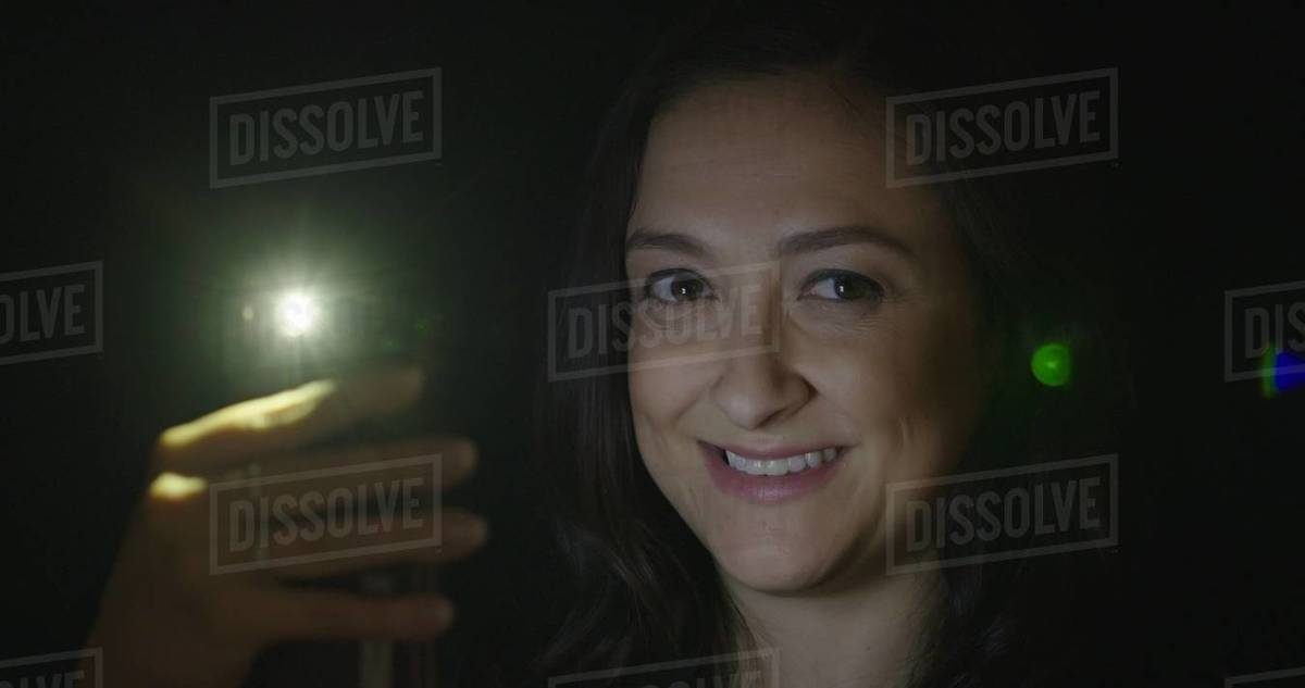 BCU young woman smiles while using cellphone at night. Phone light creates lens flares Royalty-free stock photo