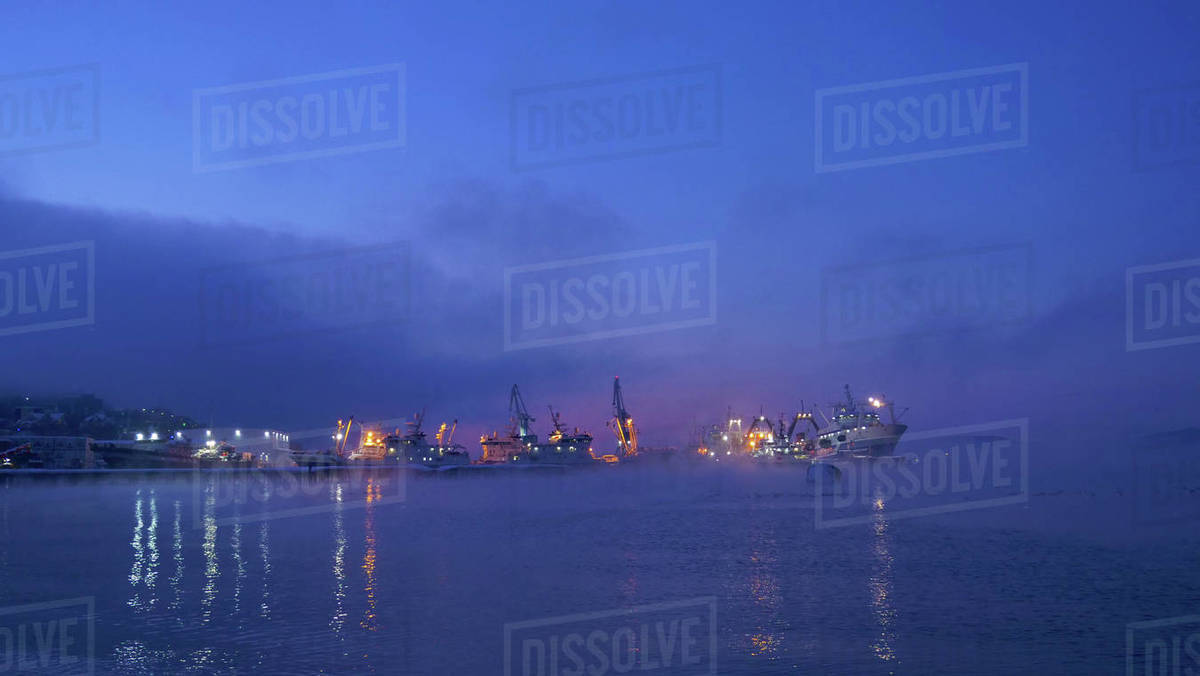 Early in the morning at dawn in the fog fishing ships are in the port of Petropavlovsk Kamchatsky Royalty-free stock photo