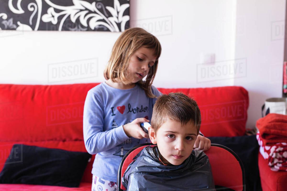 Girl cutting her brother's hair during the coronavirus quarantine Royalty-free stock photo