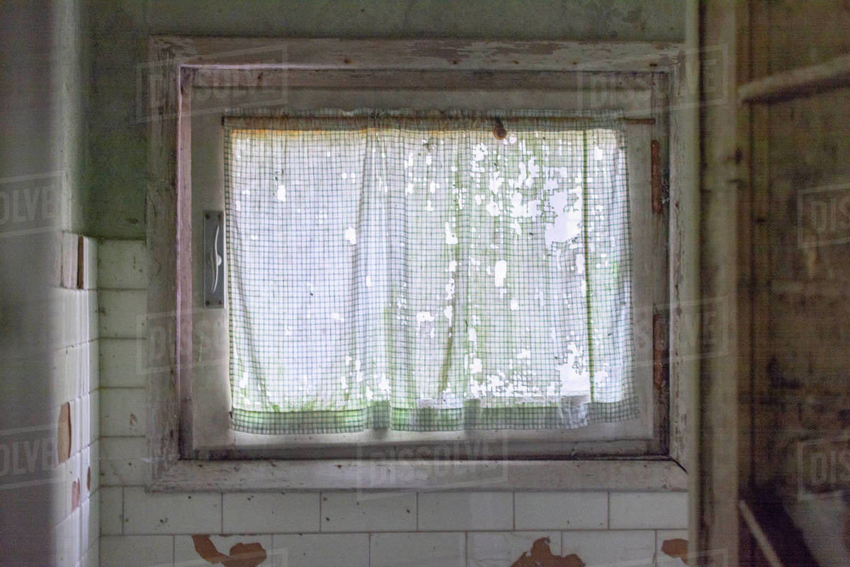Old window in the old abandoned and creepy house with curtain and forest outside Royalty-free stock photo
