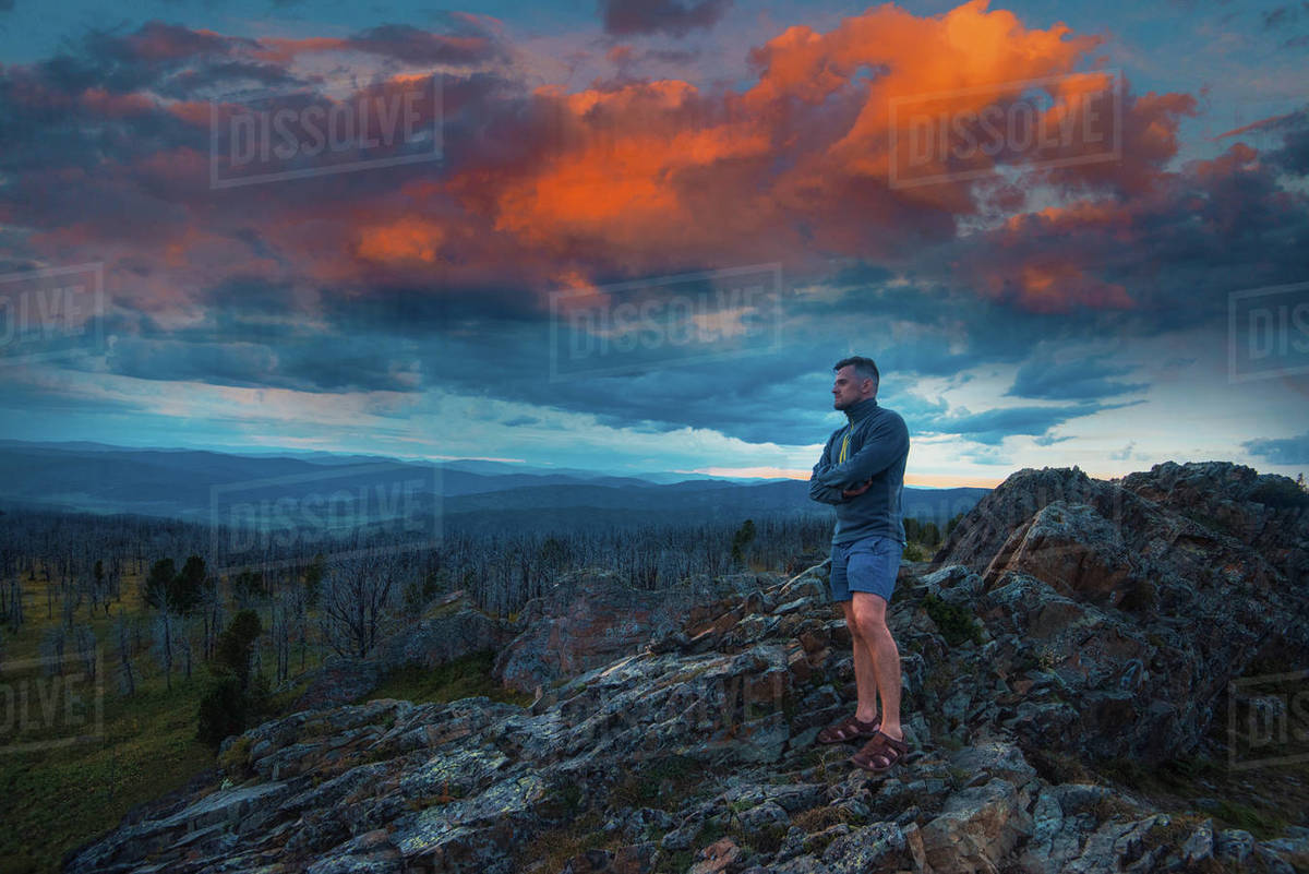 Travel, freedom and tourism concept - man standing on top of cliff in summer beauty evening in Altai mountains, fantastic sunset Royalty-free stock photo