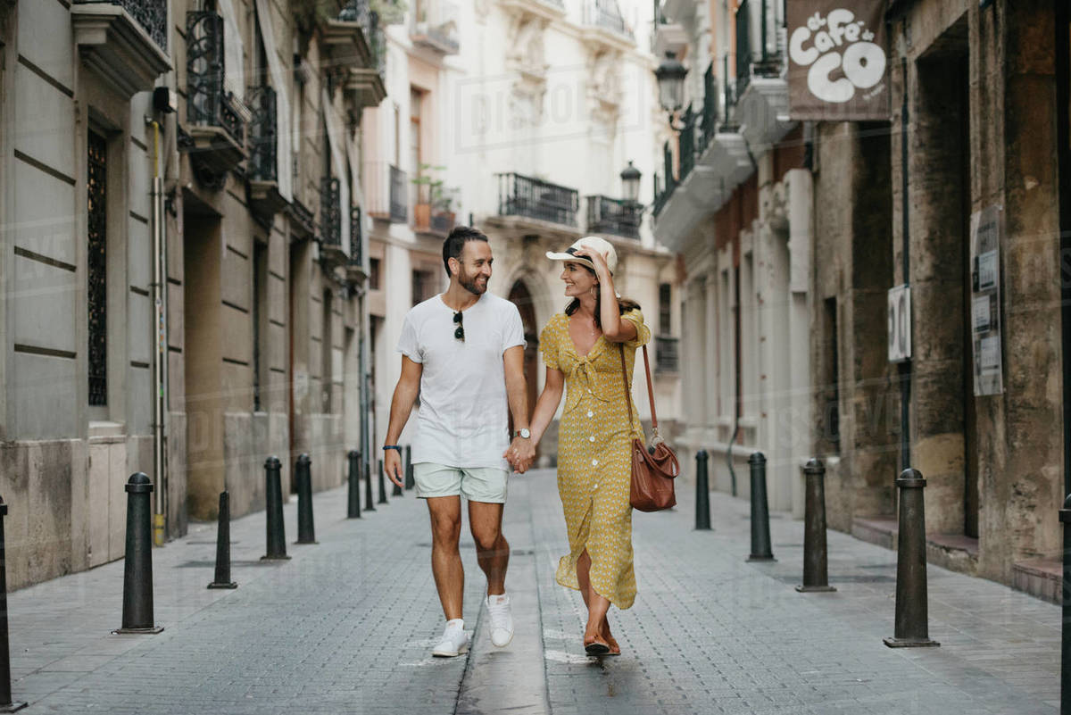 Stylish brunette girl in the hat and her boyfriend with a beard are walking together in the center of the old European street in Spain in the evening. A couple of young tourists enjoy Valencia. Royalty-free stock photo