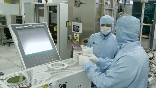 Southampton Nanofabrication Centre. Footage of nanotechnology researchers in a clean room discussing the design of a semiconductor form of a nanoscale technology. This work is being carried out at the Southampton Nanofabrication Centre, in collaboration with the University of Southampton. Footage filmed in 2016. Rights-managed stock video