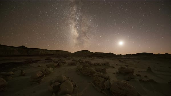 Milky Way over badlands. Time-lapse footage of the Milky Way emerging in the night sky in the fading twilight as the Moon sets over eroded rock formations in a badlands area. This landscape is in the Bisti/De-Na-Zin Wilderness, New Mexico, USA. Rights-managed stock video