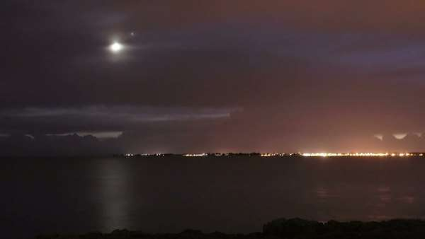 Timelapse film of the moon and Jupiter getting closer to the horizon with the clouds passing. Filmed above the coast of Brittany and the ocean. Rights-managed stock video