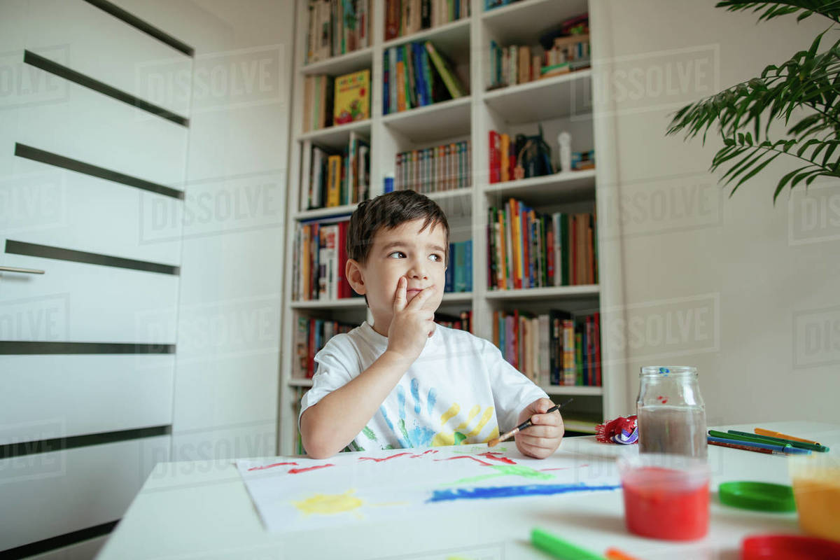 Preschooler looking for inspiration while painting. Thinking child with paintbrush and colorful paints at home. Royalty-free stock photo
