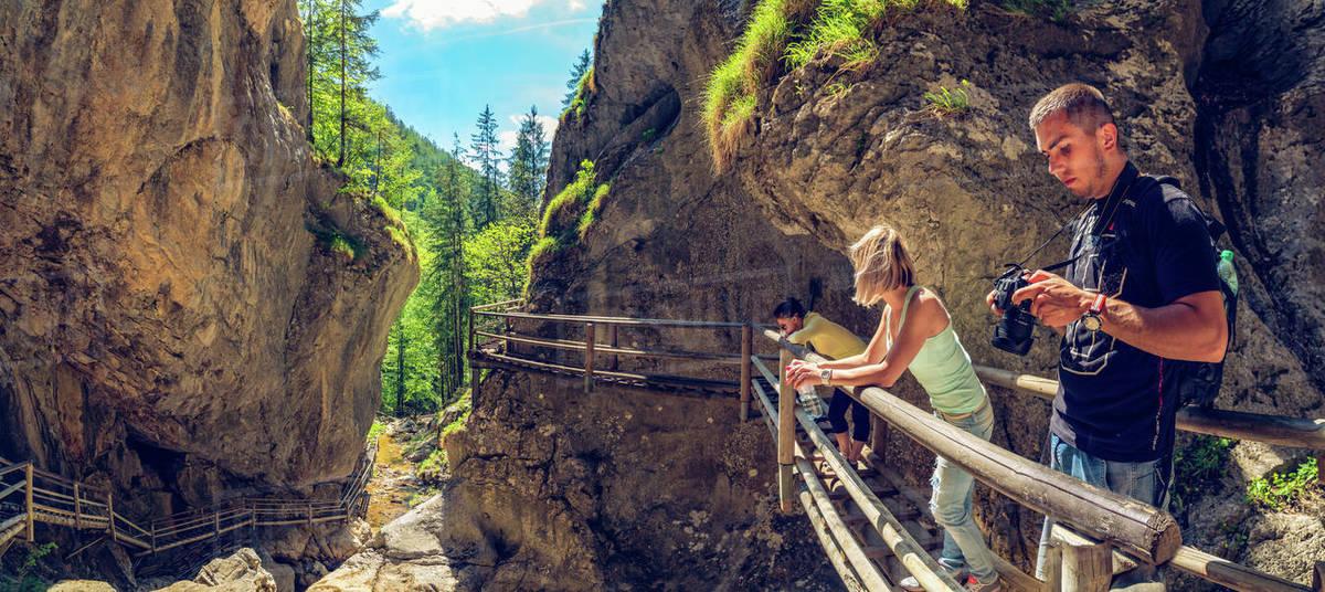 Mixnitz, Pernegg/Mur, Styria, Austria - 18.05.2017: View at waterfall path along mountain stream. People walking along stream on wooden bridge. Tourist spot. Travel destination Royalty-free stock photo