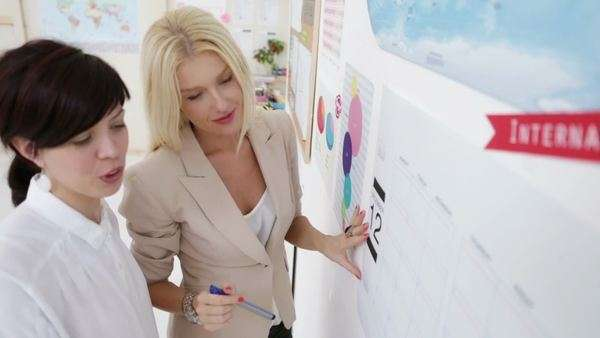 Two businesswomen writing on the wall calendar at their office. Royalty-free stock video