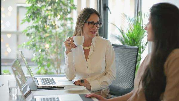 Two businesswomen chatting at their office during the coffee break. Royalty-free stock video