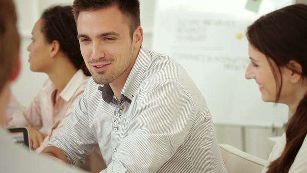 Smiling Caucasian businessman chatting with his colleagues at work. Royalty-free stock video