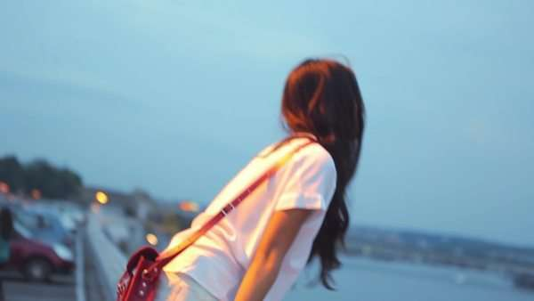 Young Asian woman looking at a river at sunset. Royalty-free stock video