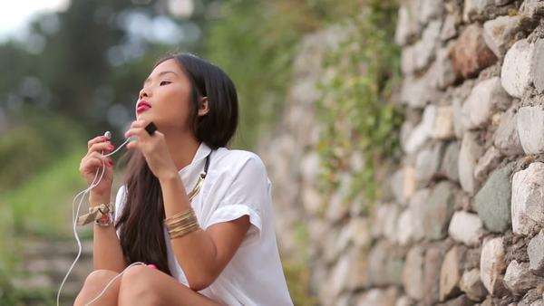 Young Asian woman listening to music on her mobile phone outdoors. Royalty-free stock video