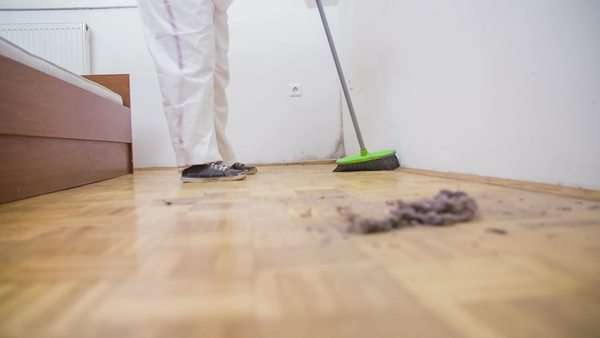sweeping floor dust with broom in slow motion low angle close up of person in