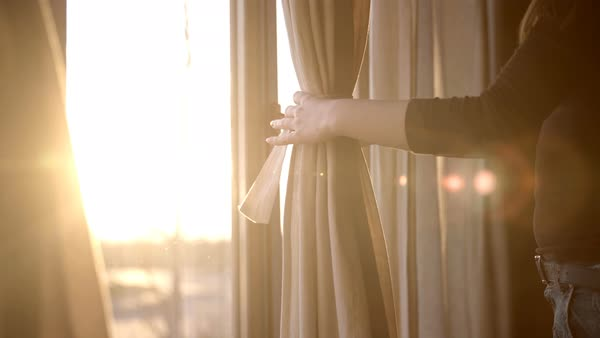 Sunrise Sun Shining Through Window While Female Person Carefully Tie Up  Huge Curtain On Window.