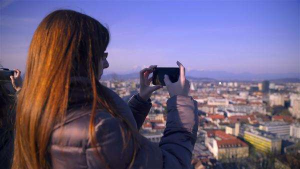 Woman photographing Ljubljana city scape from castle. Over the shoulder of female person with long brown hair holding smartphone device and take picture of city from above on a sunny day. Royalty-free stock video