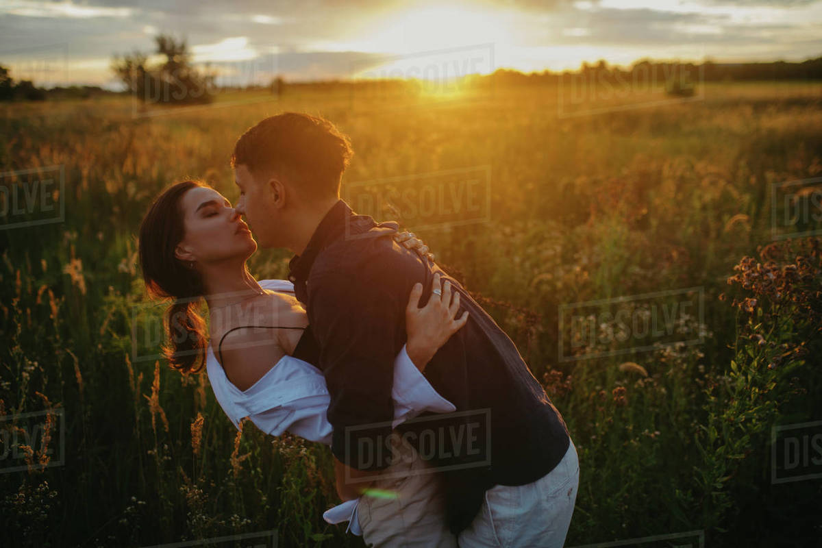 Young couple in love embraces and kisses on meadow at sunset. Backlit. Royalty-free stock photo