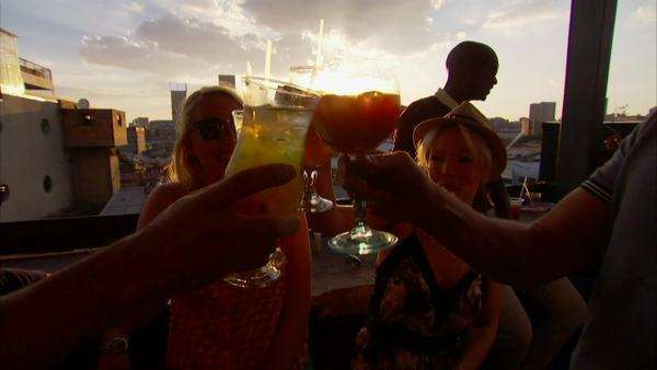 Handheld shot of a group of people drinking cocktails while overlooking the sun setting over Johannesburg Rights-managed stock video