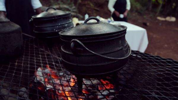 Handheld of potjie pots cooking on open fire Rights-managed stock video