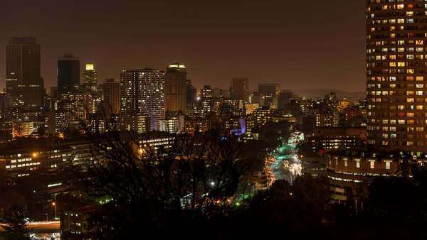 Medium night timelapse panning across Ponte Towers and the city centre of Johannesburg during peak traffic with streets and buildings, South Africa Royalty-free stock video