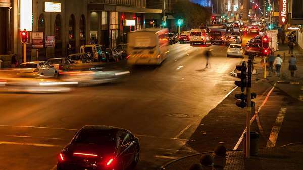 Timelapse slowly panning up at a busy intersection at night with traffic and people crossing in Ghandi Square, mid city Johannesburg, South Africa Royalty-free stock video