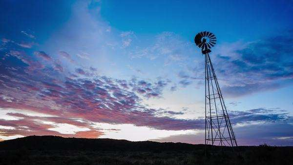 Dramatic linear timelapse sunrise with scattered clouds changing color and a silhouetted windmill in the foreground Royalty-free stock video