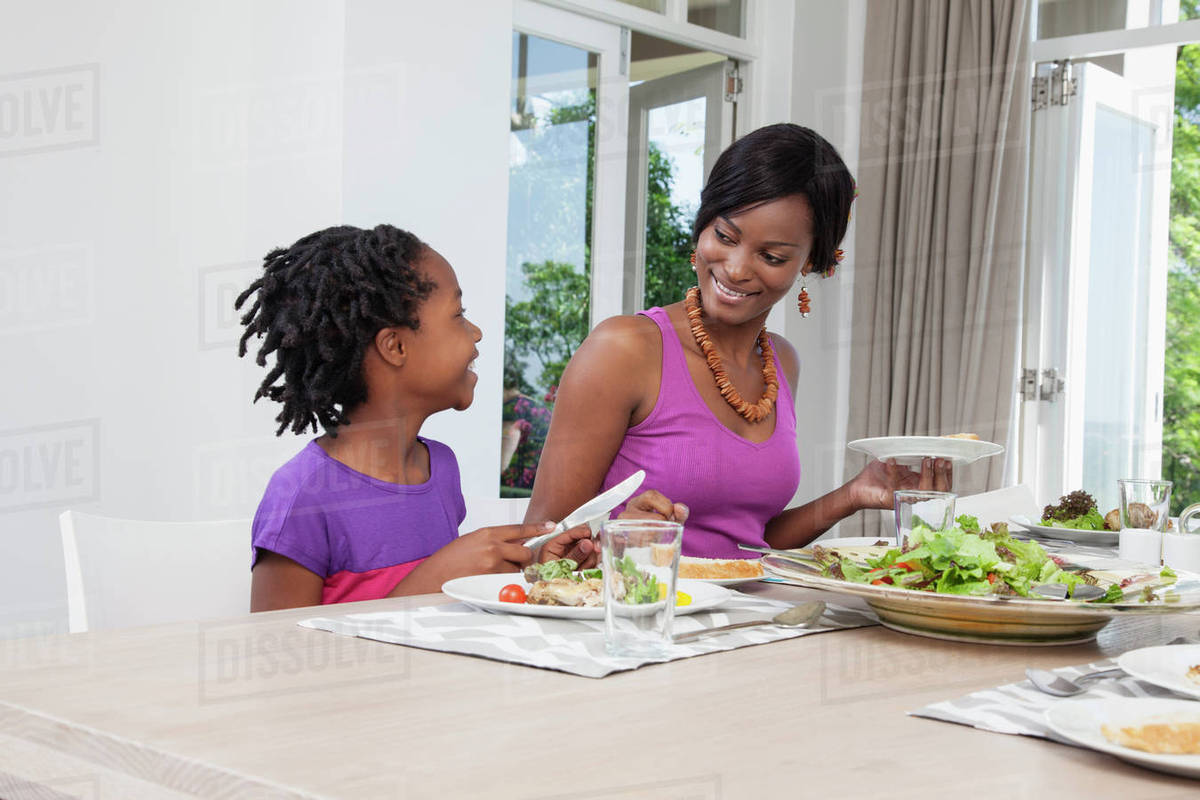 Mother and daughter eating dinner stock photo