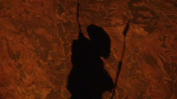Panning medium close up of shadow of bushman walking past rock carving Rights-managed stock video
