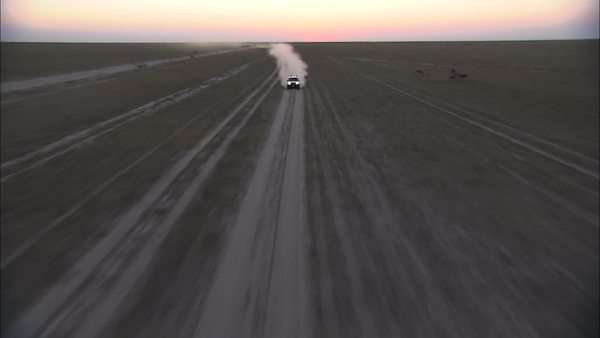 Aerial shot of a car driving across the Makgadikgadi Pan Rights-managed stock video