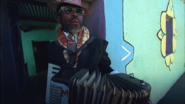Hand held shot of a man dressed in colourful clothes playing an accordion in front of a colourfully painted house Rights-managed stock video