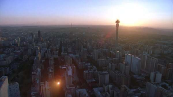 Aerial shot over Johannesburg Central Business District with the Hillbrow Tower towering above and passing the Ponte Tower during sunset/sunrise Rights-managed stock video
