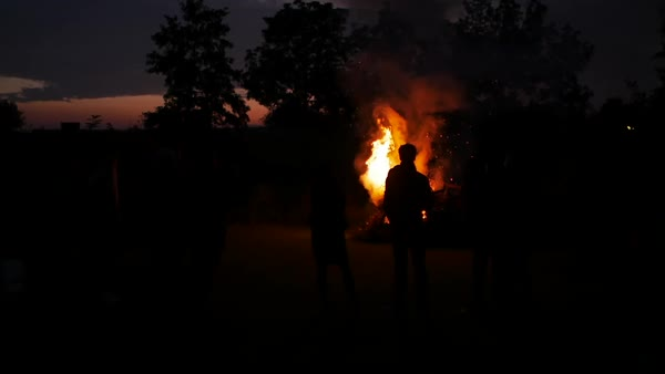 Hand-held shot of people standing by a bonfire at night Royalty-free stock video