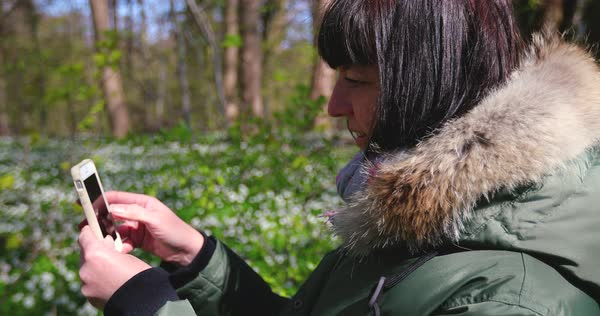 Hand-held shot of a woman using her cell phone in a forest Royalty-free stock video