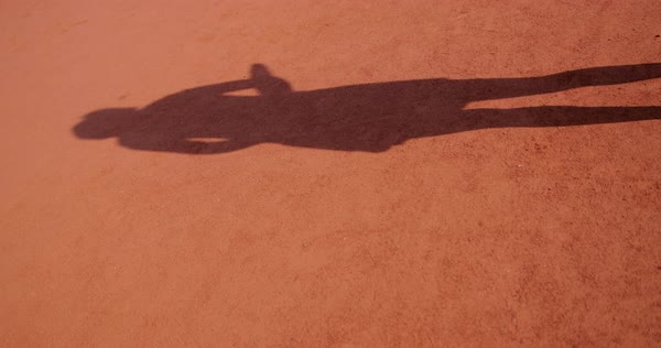 Hand-held shot of shadow of a woman playing tennis Royalty-free stock video