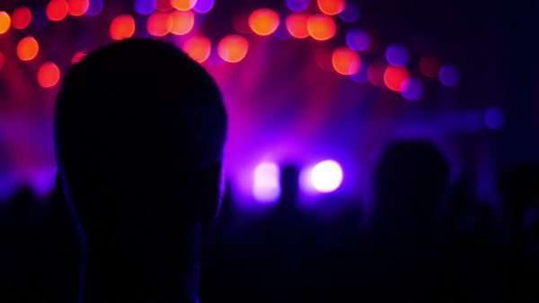 Moving shot of male at rock concert, view from behind against defocus flashing bright stage light Royalty-free stock video
