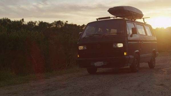A surfer pulls up in a camper van with a board on top at daybreak on a dirt road in a coastal area Royalty-free stock video
