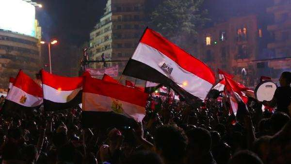 Protestors wave the Egyptian flag in Cairo, Egypt at a large nighttime rally Royalty-free stock video