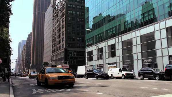 Yellow cabs, buses, and other traffic pass on a busy street in New York City Royalty-free stock video